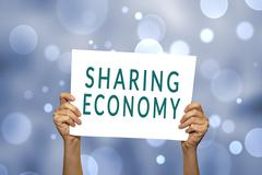 Stock Photo of SHARING ECONOMY card in hand with abstract light background.