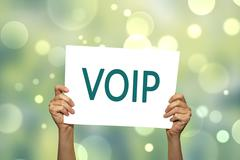 VOIP (voice over internet protocol) card in hand with abstract light backgrou - stock photo