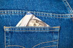 Folded dollar bills sticking out of the blue jeans pocket - stock photo