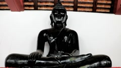 Black Buddha statue sitting in a Buddhist monastery Stock Footage