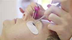 Applying lashes on eyes with tweezers 4K - stock footage