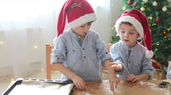 Two cute children, preparing gingerbread cookies for Christmas Stock Footage