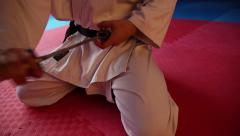 Young martial arts fighter with katana siting in seiza position Stock Footage