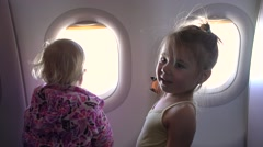 Two little sisters excitedly and joyfully looking out the airplane window Stock Footage