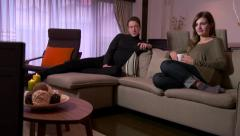 Husband And Wife Watching TV Movie Film Laughing On Couch - stock footage