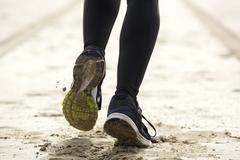 Woman feet running on sand - stock photo