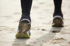 Close up rear view of female feet running - stock photo
