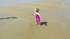 Baby jumping puddle at beach Stock Footage