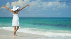 Beautiful ethnic Hispanic girl wearing white dress on ocean beach - stock footage
