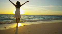 Latin American girl walking barefoot by a tropical ocean at sunset Stock Footage