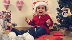 Adorable baby with red hat playing with Christmas presents beside the tree Stock Footage