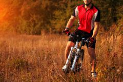 cyclist man cycling on a rural road during sunset - stock photo