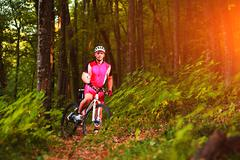 Cyclist man cycling on a rural road during sunset Stock Photos