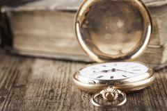 Vintage pocket watch and book on wood still life Kuvituskuvat