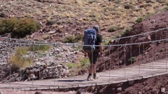 A man walks on the suspension bridge. Patagonia Stock Footage
