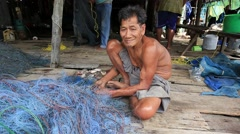 Old Thai man working with a fishing net in a fishing village Stock Footage