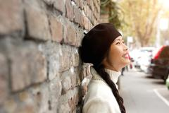 Happy young woman standing outside with beret - stock photo