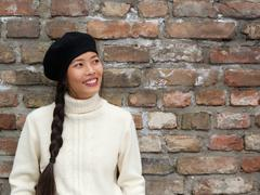 Attractive young woman smiling with beret hat - stock photo