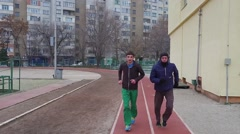 Two male athletes running on a track during the training toward the camera Stock Footage