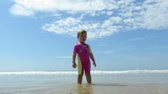 Baby standing in ocean seaside Stock Footage