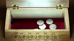 Different coins falling into the wooden casket Stock Footage