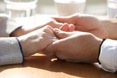 Male and female holding hands over table - stock photo