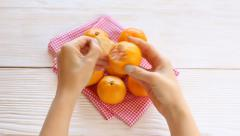 young woman peel tangerine - stock footage