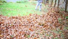 MAN BLOWING LEAVES TOWARD YOU SLO MO Stock Footage