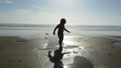 Baby touching puddles at beach Stock Footage