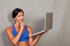 Good-looking lady wearing tank top holding laptop with hand on chin while loo - stock photo