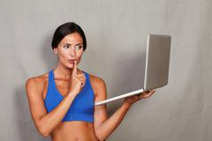 Stock Photo of Caucasian ethnicity female gesturing keep quiet while holding laptop computer