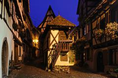 Half-timbered houses on a narrow street in Eguisheim at night, Alsace, France - stock photo