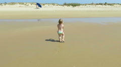 Baby walking back and picking sea shells Stock Footage