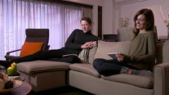 Young Man And Woman Relax At Home With Newspaper Ipad - stock footage