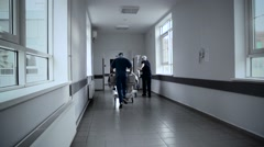Patient on stretcher pushed at speed through a hospital corridor by doctors Stock Footage