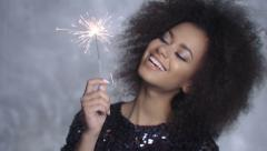 Closeup beauty portrait of young girl holding sparklers over silver background. Stock Footage