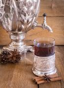Tea in glass with coaster  and russian samovar on wooden background - stock photo