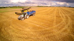 A yellow harvester and a truck fully loaded with grains Stock Footage