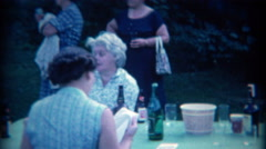 1965: Family summer outdoor socializing with alcohol ready on the picnic table. - stock footage