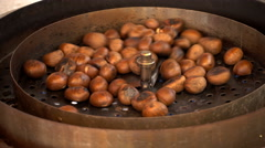 Chestnuts roasting on street vendor's stall - stock footage