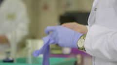 Putting on blue surgical gloves - stock footage