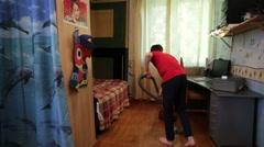 Teen boy vacuuming the floor in the room Stock Footage