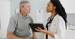 African woman doctor talking with senior patient in the office Stock Photos