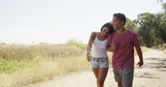 Sweet Mexican couple walking along trail and holding hands Stock Footage