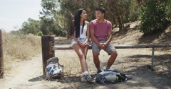 Mexican couple sitting down to rest after hike - stock footage