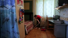 Teenager vacuuming the floor in the room Stock Footage
