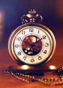 retro gold pocket watch in beautiful light candle on brown background - stock photo
