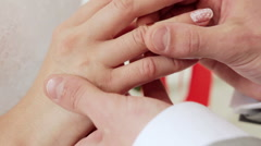 Putting wedding ring on bride finger Stock Footage