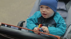 Child is sitting in a carriage and talking, Slowmotion Stock Footage