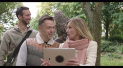4K Visitors to a falconry centre taking a selfie with grey owl behind them Stock Footage